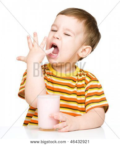 Cute little boy with a glass of milk licking his finger, isolated over white