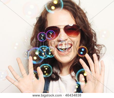 happy young woman wearing sunglasses with soap bubbles