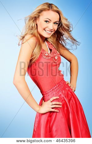Portrait of a charming smiling young woman in red summer dress.