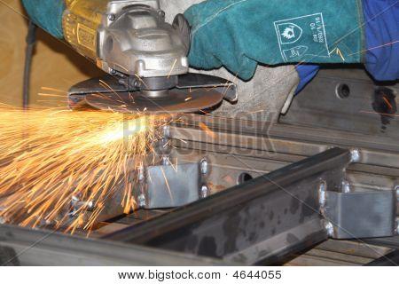 Labourer Grinding A Piece Of Metal
