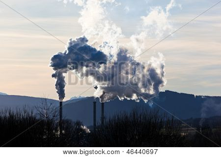 the smoking chimneys of a factory against a blue sky. white smoke rises from chimneys on
