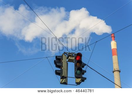 chimney of an industrial company and a red traffic light. symbolic photo for environmental protection and ozone.