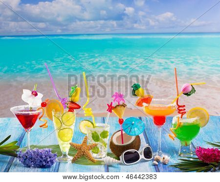 Colorful many tropical Cocktails in tropical blue wood at turquoise beach with coconut mojito margarita