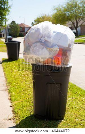 Trash bin dustbin full of excess garbage on street lawn