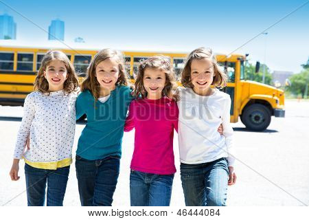 school girls friends sisters in a row walking from yellow school bus lot