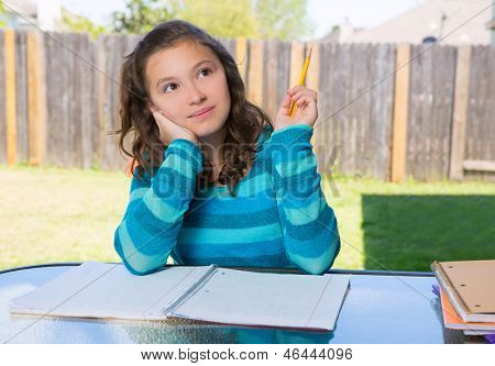 American latin teen girl thinking with pencil doing homework on backyard