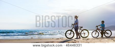 Panorama of mother and son biking on a beach at sunset