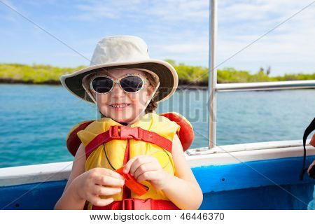 Adorable little girl in a life jacket traveling on boat