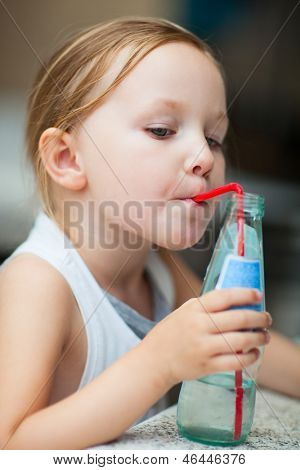 Adorable little girl drinking water from a bottle using a straw