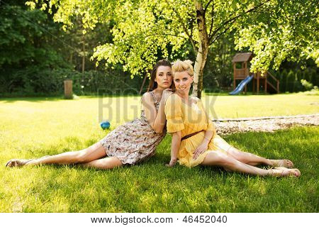 Two romantic girl sitting on flower meadow