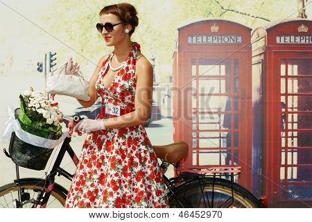 MOSCOW - AUG 5: Female participant of cycle parade Lady on Bicycle at Sokolniki park stands near phone booth, August 5, 2012, Moscow, Russia.