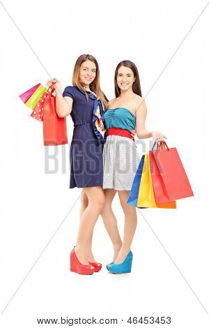 Full length portrait of two female friends holding shopping bags and posing isolated on white background