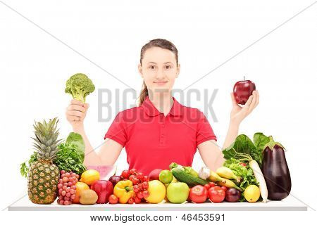 Smiling female teenager sitting and holding apple and broccoli on a table full of various vegetables and fruits isolated on white background