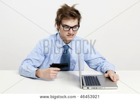Young man in the office and pointing a gun to the laptop