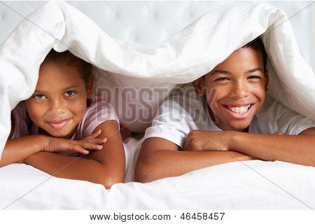 Zwei Kinder, die unter der Bettdecke im Bett versteckt