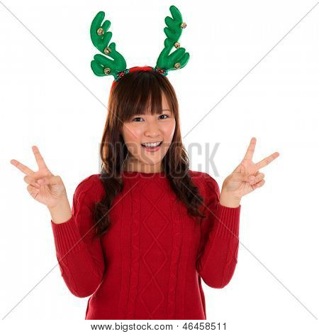 Asian Christmas girl showing victory sign. Lovely young girl gestures v fingers smiling happy isolated on white background.
