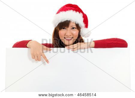 Christmas girl showing blank billboard banner sign smiling happy. Beautiful and cute Asian female model isolated on white background.