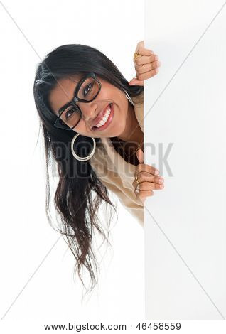 Indian businesswoman peeking from behind blank sign billboard. Advertising photo of smiling India woman showing paper sign. Asian female model isolated on white background