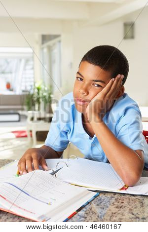 Fed Up Boy Doing Homework In Kitchen