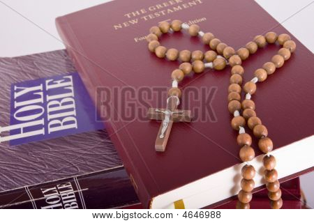 Holy Bible With Rosary On Pile Of Old Books