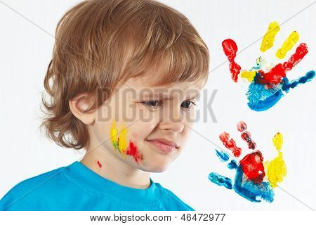 Dissatisfied boy with painted face on background of hand prints
