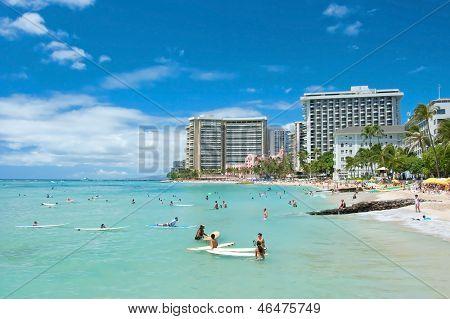 Tourist Sunbathing And Surfing On The Waikiki Beach In Hawaii.