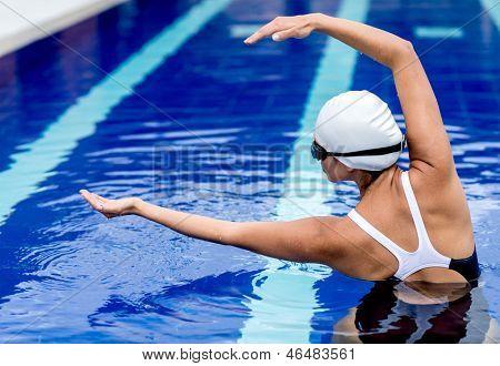 Nadadora femenina en el estiramiento de la piscina