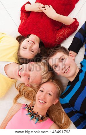Brothers and sisters lying on a floor together
