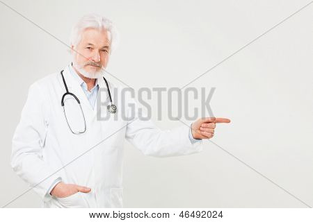 Handsome elderly doctor in uniform isolated over light background