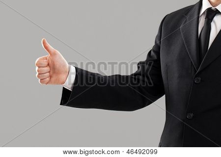 Businessman's torso in suit with thumb up over grey background