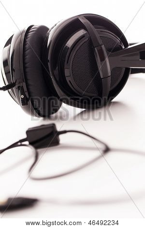 Closeup image of big black headphones on a white background