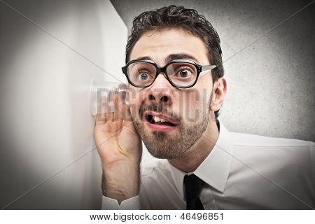 curious businessman listens with glass leaning against the wall