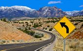 stock photo of hazard  - A road sign alerts motorists to a curving mountain road in northern New Mexico - JPG