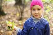 pic of face-fungus  - Smile little girl in pink hat holds maple leaf and toadstool in autumn forest - JPG