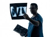 one caucasian man doctor surgeon radiologist medical examining lung torso  x-ray image silhouette is