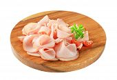Thinly sliced turkey ham on cutting board