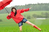 stock photo of dancing rain  - Playful happy girl in the rain with red umbrella - JPG