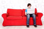 Man Sitting On Couch With Laptop