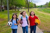 Children kid girls walking to school with sport balls folders and backpacks in outdoor park