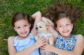 image of chihuahua  - twin sisters playing with chihuahua dog lying on backyard lawn - JPG