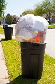 Trash bin dustbin full of excess garbage on street lawn