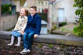 image of brother sister  - Brother and sister outdoors in city on beautiful spring day - JPG