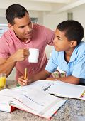 stock photo of 11 year old  - Father Helping Son With Homework In Kitchen - JPG