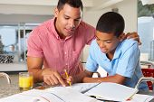 stock photo of encouraging  - Father Helping Son With Homework In Kitchen - JPG