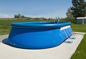 stock photo of bulge  - An above ground pool sets on a concrete pad in the backyard on a sunny summer day - JPG