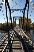 stock photo of trestle bridge  - A trestle railroad bridge crosses a river with fall colors - JPG
