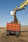stock photo of boom-truck  - A trackhoe loads a truck with dirt - JPG