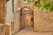 stock photo of cobblestone  - Narrow cobbled street among traditional stoned houses of jewish quarter at old historic part of jerusalem - JPG