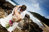 image of wedding couple  - Passionate young couple getting married on the beach standing on rocks - JPG