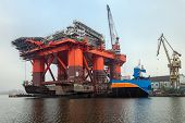 stock photo of oil derrick  - Weighing in at 12 thousand ton Oil Rig was pulled from the water on a special barge to be able to repair the underwater part - JPG